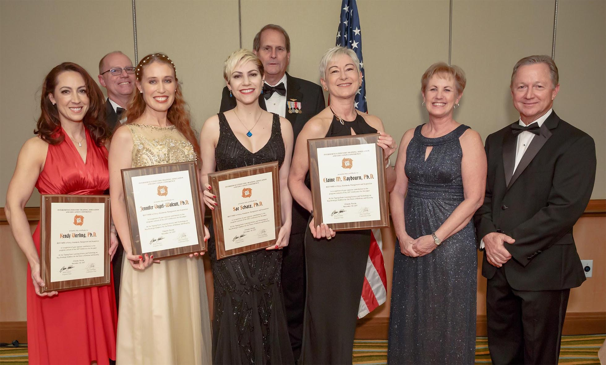"The authors receiving their ""Best Policy Subcommittee Paper"" award, left to right: Kendy Vierling, Ph.D., Jennifer ""JJ"" Vogel-Walcutt, Ph.D., Sae Schatz, Ph.D., and Elaine M. Raybourn, Ph.D. with the IITSEC 2017 Leadership."